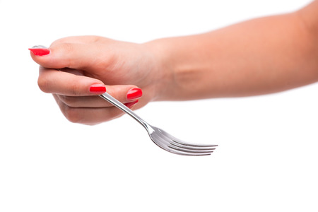 hardships: Woman with nice red polished nails holding a metal fork in her hands. Isolated on white background Stock Photo