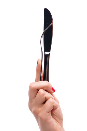 hardships: Woman with nice red polished nails holding a metal fork with the knife together in her hands. Isolated on white background
