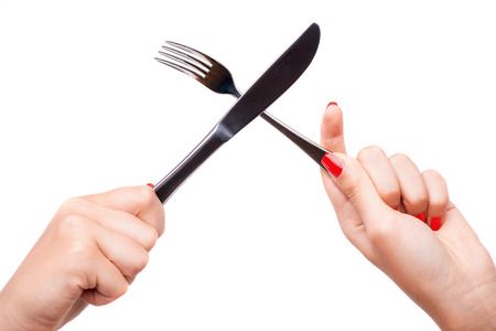 hardships: Woman with nice red polished nails holding a metal fork crossing with the knife in her hands. Isolated on white background
