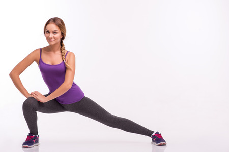 knee bend: Healthy young sportswoman does the exercises standing with wide legs  bend knee and holding hands on knee isolated on white background with copy place