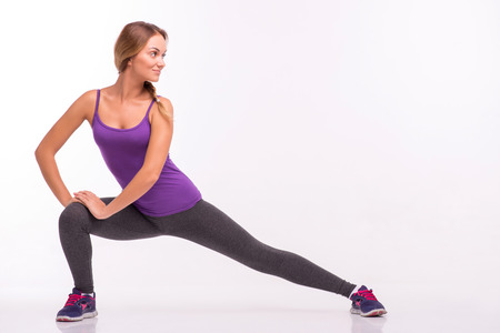 knee bend: Healthy young sportswoman does the exercises standing with wide legs  bend knee and holding hands on knee looking away isolated on white background with copy place
