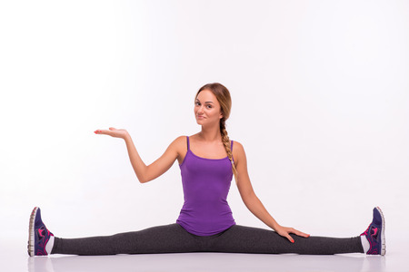 Healthy young sportswoman does the exercises doing the splits looking and holding one hand up and another one on knee isolated on white background with copy place photo