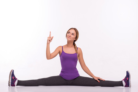 Healthy young sportswoman does the exercises doing the splits looking and holding one hand up and putting aside isolated on white background with copy place photo