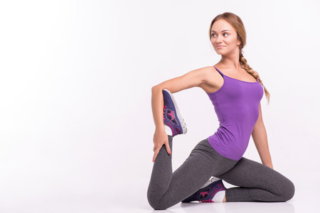 banding: Healthy young sportswoman does the exercises sitting  banding one leg back  isolated on white background with copy place Stock Photo