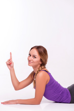 aside: Healthy young sportswoman does the exercises lying on stomach leaning on hands  looking at the camera putting aside  isolated on white background with copy place side view