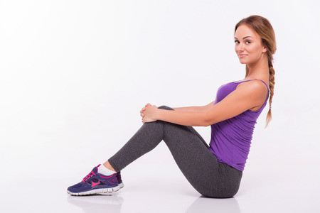 back straight: Sportswoman does the exercises sitting  and holding  her back straight and hands on her knees   isolated on white background with copy place side view