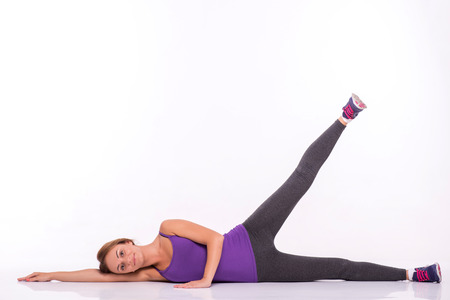 Healthy young sportswoman does the exercises lying on side raising one leg  looking at camera   isolated on white background with copy place photo