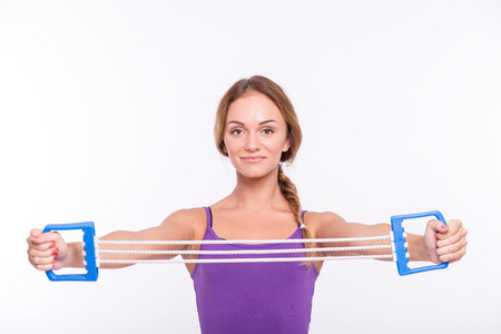 Healthy young sportswoman does the exercise working  out  triceps holding in  hands elastic isolated on white background with copy place waist up photo