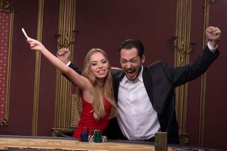 casino dealer: Happy handsome  man  smiling winning and beautiful woman looking at camera  in casino sitting at table with red white and blue piles of chips  waist up