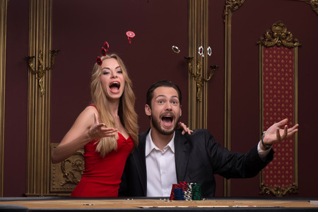 Happy handsome  man  smiling winning and beautiful woman looking at camera  in casino sitting at table tossing up white and red chips  waist up