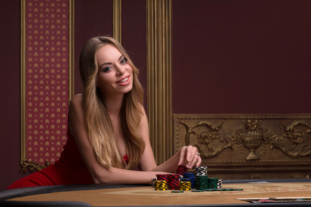 beautiful woman looking at camera  in casino sitting at table with  white blue and red chips  in piles waist up
