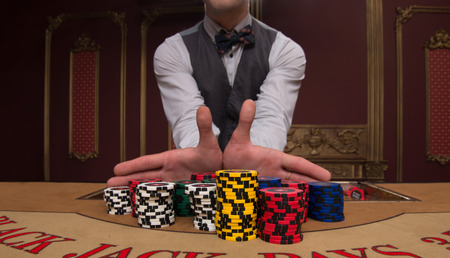 casino dealer: Handsome  dealer giving  red blue and shite chips in piles  on  table with  in casino looking at camera