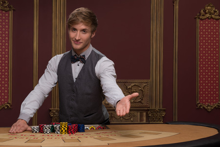Handsome  dealer  inviting for game showing chips near table with  red blue and white chips in piles in casino