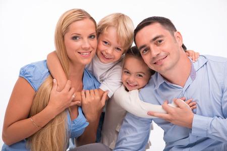 Gelukkige familie van vader moeder zoon en dochter glimlachen hurken kijken camera geïsoleerd op een witte achtergrond taille Stockfoto - 33192890