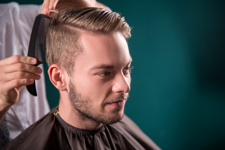 peluquero: peluquero hace el pelo con el peine negro de cliente satisfecho guapo en peluquer�a profesional