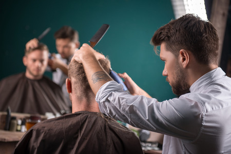 hairdresser  cuts    hair  with hair clipper on back of the head of handsome satisfied  client in  professional  hairdressing salon photo