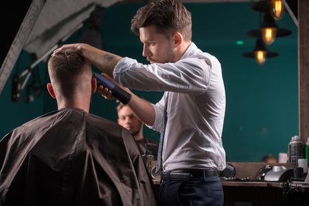 peluqueria: peluquero corta el pelo con cortadora de cabello en la parte posterior de la cabeza del cliente satisfecho guapo en ángulo inferior de peluquería profesional