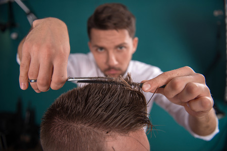 barber: hairdresser  cuts   hair  with scissors on crown of handsome satisfied  client in  professional  hairdressing salon Stock Photo