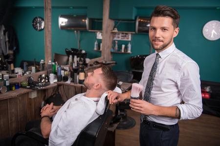 peluqueria: peluquería con el cepillo y el cliente satisfecho hermoso con corte de pelo corto en el salón de peluquería profesional Foto de archivo