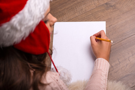 brown haired girl: Beautiful attractive brown haired girl pending Christmas dressed in cap of Santa Claus  laying on stomach writing congratulation  letter on white clear paper