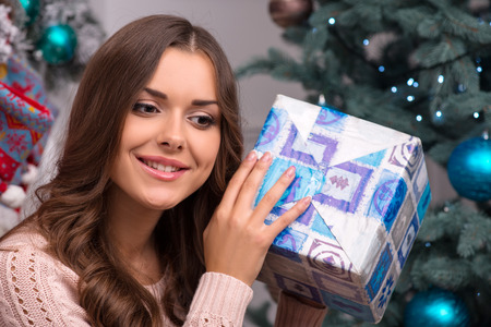 divining: Beautiful attractive brown haired girl sitting near fir tree  holding in hands and   divining present in blue gift wrapping dressed in beige knitted jacket Stock Photo