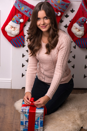 brown haired girl: Beautiful attractive brown haired girl sitting near red Christmas socks for presents  dressed in beige knitted jacket with present in blue gift wrapping Stock Photo