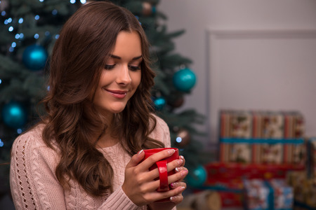 knitted jacket: Beautiful attractive brown haired girl drinking cup of coffee or tea or milk sitting near fir tree and heap of  presents  dressed in beige knitted jacket selective focus  looking at cup