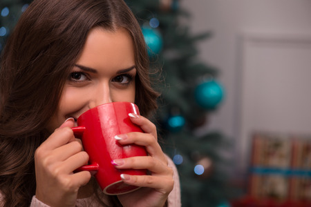 knitted jacket: Beautiful attractive brown haired girl drinking cup of coffee or tea or milk sitting near fir tree and heap of  presents  dressed in beige knitted jacket selective focus  looking at camera Stock Photo
