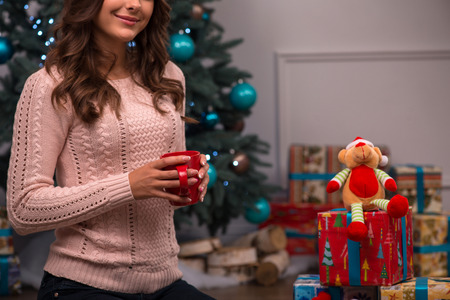 knitted jacket: Beautiful attractive brown haired girl sitting near red Christmas socks for presents and fir tree and heap of  presents  on white pile carpet dressed in beige knitted jacket