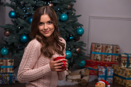brown haired girl: Beautiful attractive brown haired girl sitting with red cup near red Christmas socks for presents and fir tree and heap  present in blue gift wrapping on white pile carpet Stock Photo