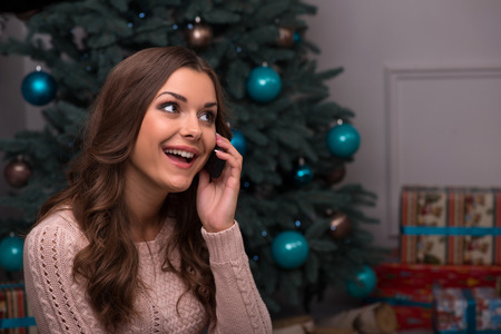 brown haired girl: Beautiful attractive brown haired girl sitting fir tree and heap of  presents  in different  gift wrapping on white pile carpet speaking  on  phone looking at camera