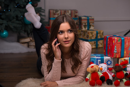 brown haired girl: Beautiful attractive brown haired girl laying on stomach near  fir tree and heap of  presents  in different  gift wrapping on white pile carpet speaking  on  phone