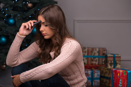 brown haired girl: Beautiful attractive sad  disappointed brown haired girl sitting  with phone near  fir tree and heap of  presents  in different  gift wrapping on white pile carpet Stock Photo