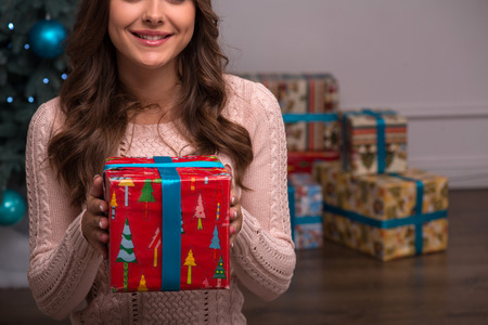 brown haired girl: Beautiful attractive brown haired girl sitting  with present  near  fir tree and heap of  presents  in red gift  wrapping and blue ribbon on white pile carpet Stock Photo