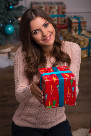 brown haired girl: Beautiful attractive brown haired girl giving   present  in red gift  wrapping and blue ribbon  near  fir tree and heap of  presents  on white pile carpet Stock Photo