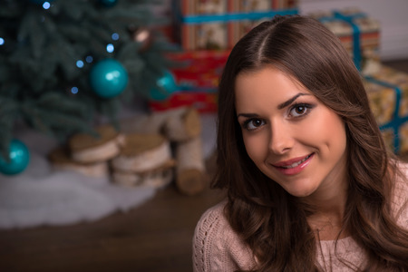 brown haired girl: Beautiful attractive brown haired girl sitting  near  fir tree and heap of  presents  in different gift  wrapping dressed in beige knitted jacket looking aside