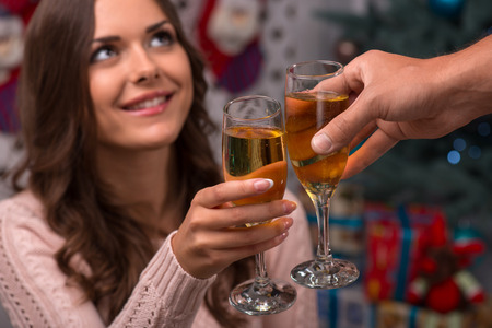 knitted jacket: Two glasses of champagne in hand of beautiful attractive brown haired girl sitting  near  fir tree and heap of  presents  in different gift  wrapping dressed in beige knitted jacket Stock Photo
