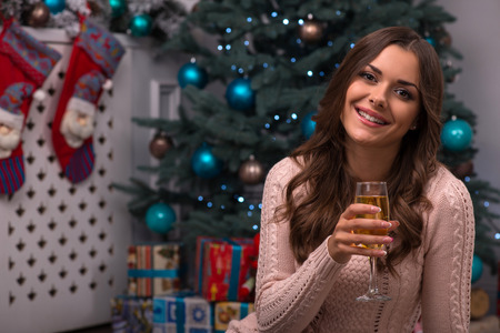 brown haired girl: Beautiful attractive brown haired girl sitting with two glasses of champagne near red Christmas socks for presents and fir tree on white pile carpet dressed in beige knitted jacket