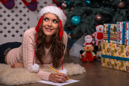 brown haired girl: Beautiful attractive brown haired girl pending Christmas dressed in cap of Santa Claus  laying on stomach writing congratulation  letter on white clear paper looking aside Stock Photo