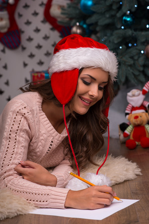 brown haired girl: Beautiful attractive brown haired girl pending Christmas dressed in cap of Santa Claus  laying on stomach writing congratulation  letter on white clear paper looking at it
