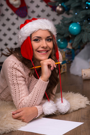brown haired girl: Beautiful attractive brown haired girl pending Christmas dressed in cap of Santa Claus  laying on stomach writing congratulation  letter on white clear paper looking at camera