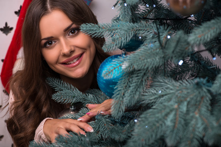 brown haired girl: Beautiful attractive brown haired girl pending Christmas  smiling dressed in beige knitted jacket  near  fir tree with blue toy  looking at camera
