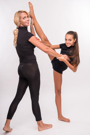 Young sport  mother and her   daughter teenager doing splits  looking at camera  isolated on white background with copy place photo