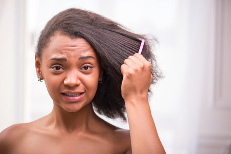 efforts: Beautiful  sad disappointed dark skinned girl being not able to  comb her hair looking at camera making efforts pulling her face isolated on white background Stock Photo