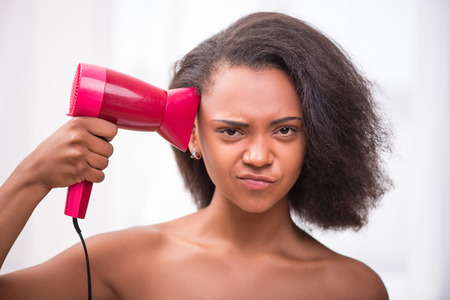 dark skinned: Beautiful  dark skinned girl blowing  dry her  hair with rose hairdryer  isolated on white background pulling face  looking at camera