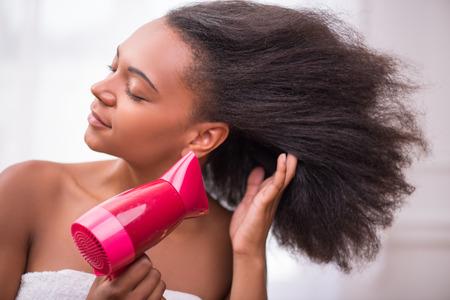 eyes closing: Hermosa ni�a de piel oscura que sopla seca el pelo con secador de pelo rosa aislados en fondo blanco cerrar los ojos