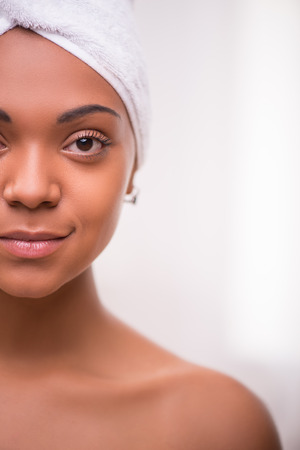 dark skinned: Portrait of beautiful  dark skinned girl in white towel on head looking at camera isolated on white background with copy place Stock Photo