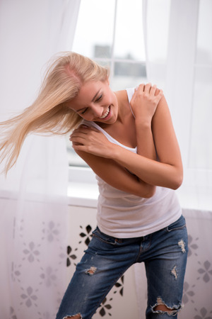 hands on waist: Beautiful happy  blond girl with flying hair in white  T shirt  and jeans and trainers smiling looking aside touching her shoulders with hands waist up