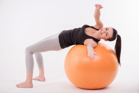 Healthy young sportswoman dong exercises lying on  orange exercise ball  smiling inviting to join  isolated on white background photo