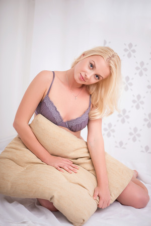 underclothes: Sexy beautiful blond girl in violet  underclothes sitting with beige pillow looking at camera full length